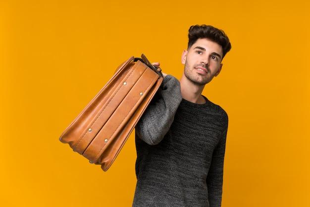 Молодой человек держит старинный портфель
