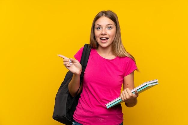Молодая девушка студента над изолированным желтым цветом удивила и указывать палец в сторону