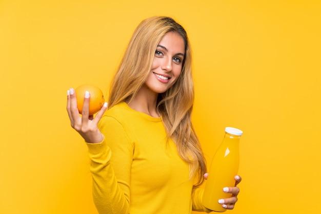 黄色の上にオレンジジュースを置く若いブロンドの女性