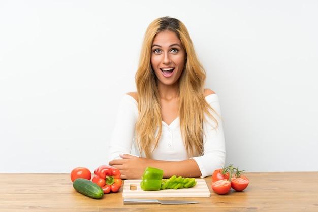 驚きの表情を持つテーブルで野菜を持つ若いブロンドの女性