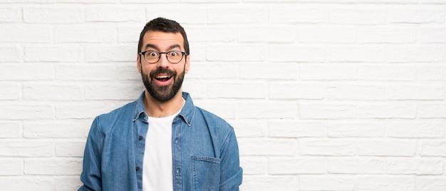 Красивый мужчина с бородой над белой кирпичной стеной с удивленным выражением лица