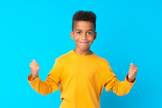 勝利を祝う分離された青い上のアフリカ系アメリカ人の少年