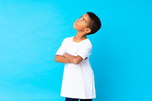 Мальчик афроамериканца над изолированной синей делая жест сомнений пока поднимающ плечи