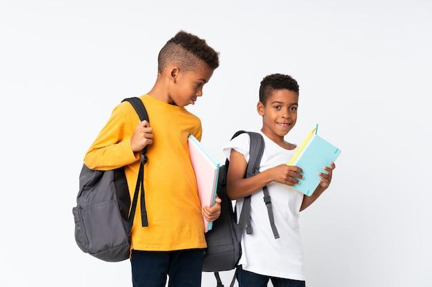 Два мальчика афро-американских студентов над изолированной белой
