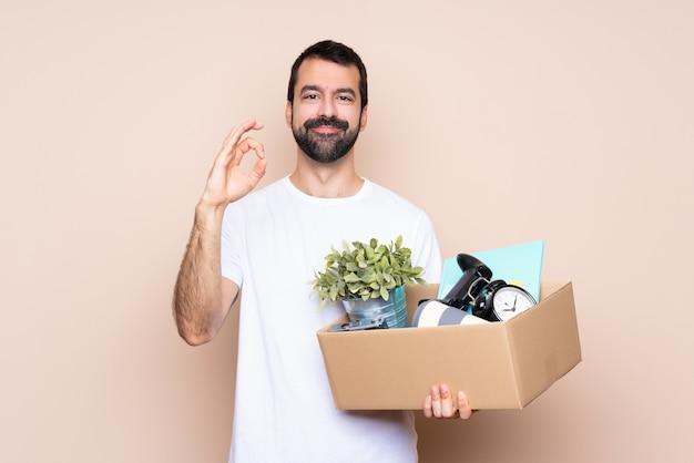 Человек держа коробку и двигая в новый дом показывая одобренный знак с пальцами