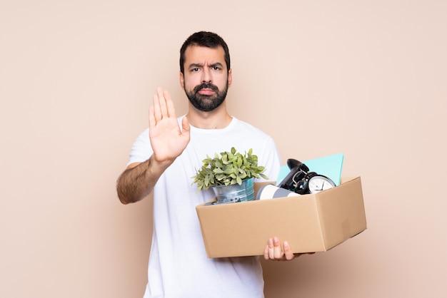 箱を抱えて停止ジェスチャーを作る新しい家に移動する男