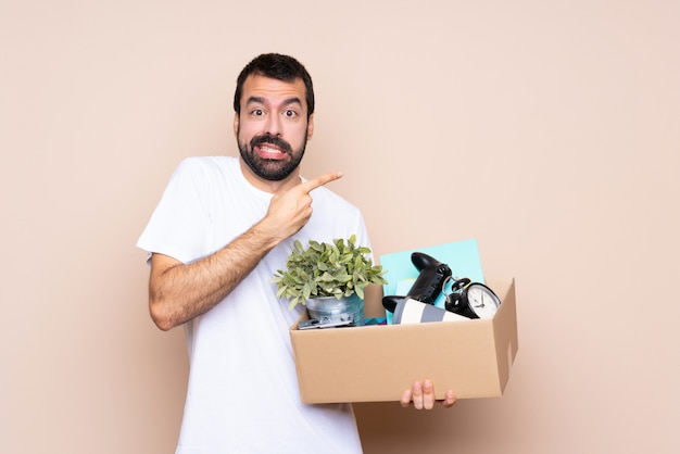 Человек, держащий коробку и двигающийся в новый дом испуганный и указывающий на сторону