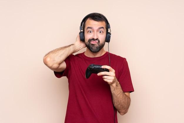 Человек играет с контроллером видеоигры над изолированной стеной, имея сомнения