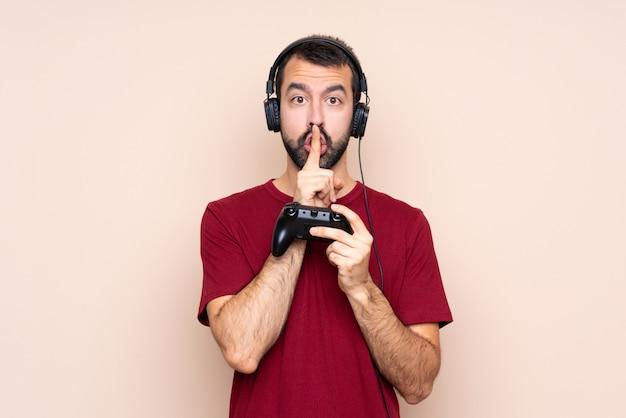 Человек играет с контроллером видеоигры над изолированной стеной, показывая знак жеста молчания, положив палец в рот