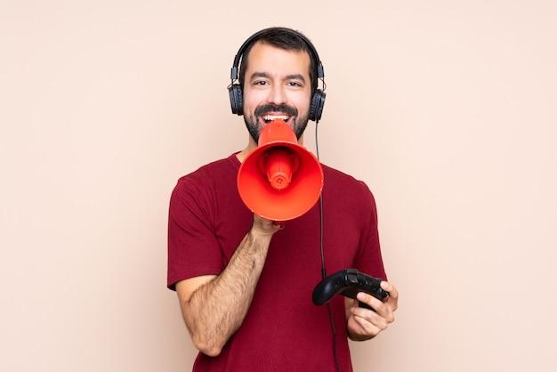 Человек играет с контроллером видеоигры над изолированной стеной, крича через мегафон