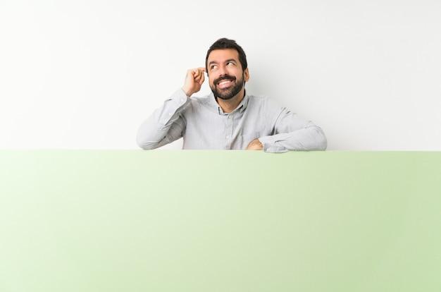 アイデアを考えて大きな緑の空のプラカードを保持しているひげの若いハンサムな男
