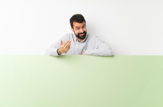 手に来るように招待して大きな緑の空のプラカードを保持しているひげの若いハンサムな男。あなたが来て幸せ