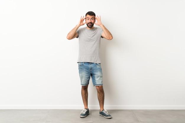Полнометражный снимок красивого мужчины с бородой с удивленным выражением лица