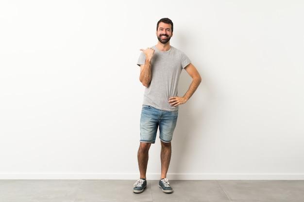 製品を提示するために横向きのひげを持つハンサムな男の全身ショット