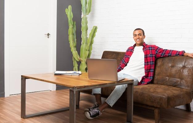 ヒップで腕でポーズと正面を見て笑っているリビングルームでラップトップを持つアフリカ系アメリカ人