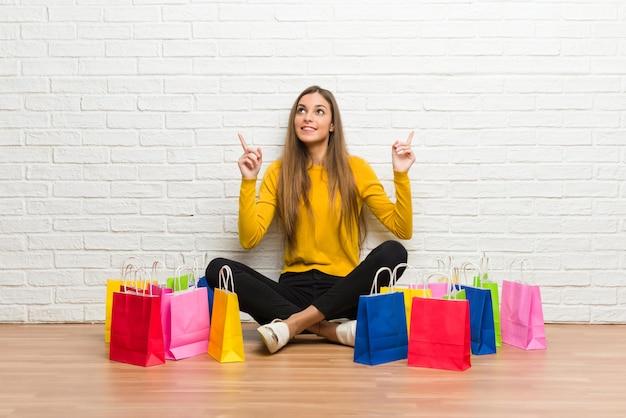 人差し指で素晴らしいアイデアを指している買い物袋の多くを持つ若い女の子