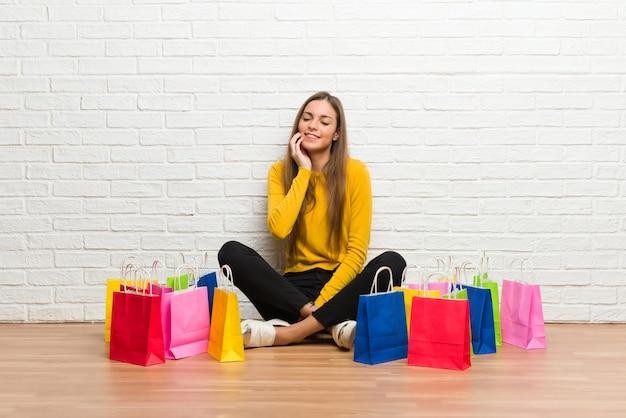 歯痛と買い物袋の多くを持つ若い女の子