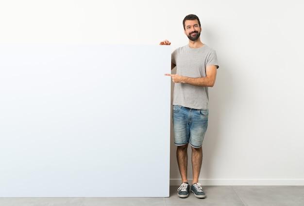製品を提示する側を指している大きな青い空のプラカードを保持しているひげの若いハンサムな男
