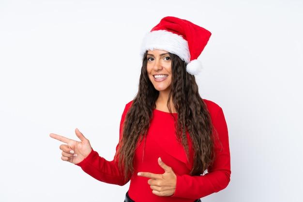 Девушка с шляпой рождества над изолированным белым указательным пальцем в сторону