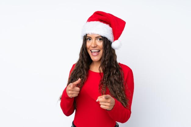 Девушка с шляпой рождества над изолированными пальцами белых точек на вас