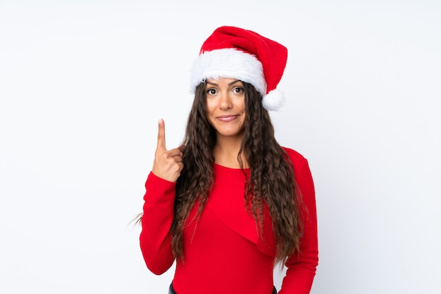 Девушка с шляпой рождества над изолированной белизной указывая с указательным пальцем отличная идея