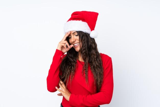 Девушка с шляпой рождества над изолированным белым смеяться над