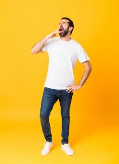 孤立した黄色のあくびと手で口を大きく開けてカバー上のひげを持つ男の全身ショット