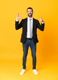 Полнометражный снимок деловой человек на изолированных желтый, показывая знак ок и большой палец вверх жест
