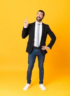 指を持ち上げながらソリューションを実現しようとしている孤立した黄色の上のビジネスマンの全身ショット