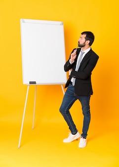 Полнометражный снимок бизнесмена, давая представление на белой доске над изолированных желтый