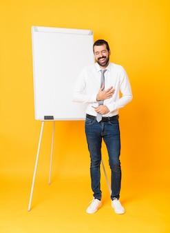 多くの笑みを浮かべて分離された黄色の上にホワイトボードでプレゼンテーションを行う実業家の全身ショット