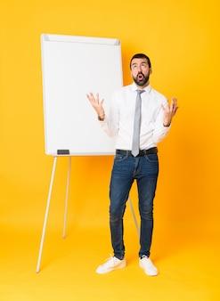 悪い状況にイライラして孤立した黄色の上にホワイトボードでプレゼンテーションを行う実業家の全身ショット
