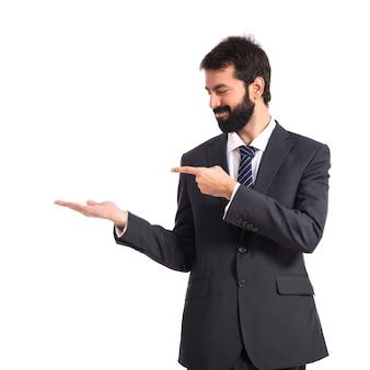 孤立した白い背景の上に何かを提示するビジネスマン