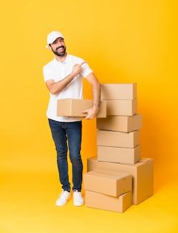 製品を提示する側を指している孤立した黄色の上のボックスの間で配達人の全身ショット