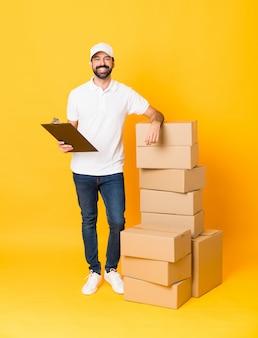 孤立した黄色の上のボックスの中で配達人の全身ショット
