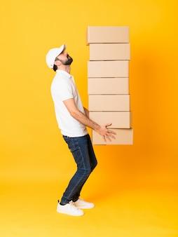 Полнометражный снимок доставщик среди коробок на изолированных желтый