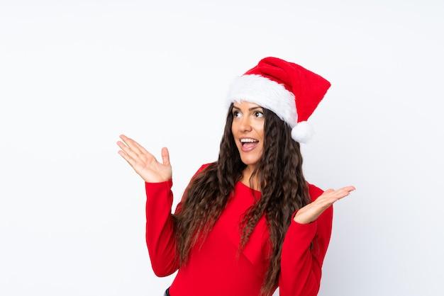 Девушка с шляпой рождества над изолированной белизной с выражением лица сюрприза