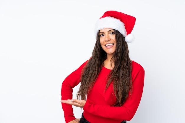 Девушка с шляпой рождества над изолированной белизной удлиняя руки в сторону для приглашать прийти