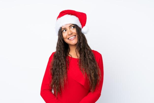 Девушка с шляпой рождества над изолированным белым смеяться над и смотреть вверх