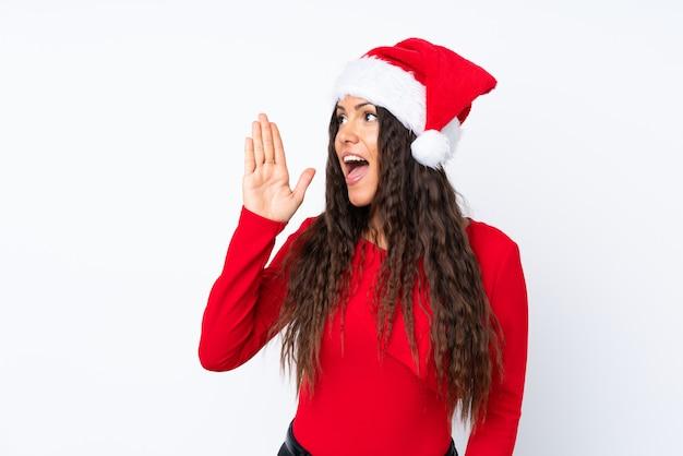 Девушка с шляпой рождества над изолированным белым кричать с широко открытым ртом