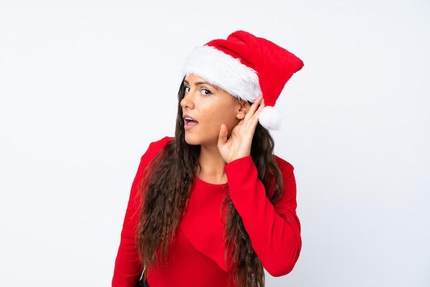 Девушка с шляпой рождества над изолированным белым слушая что-то