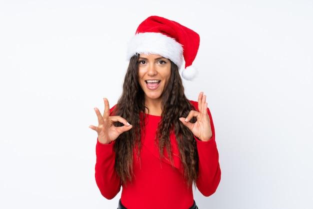 Девушка с шляпой рождества над изолированной белизной показывая одобренный знак с пальцами