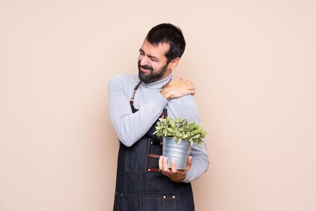 努力をしたために肩の痛みに苦しんでいる植物を抱きかかえた