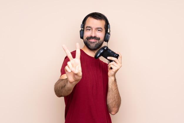 Укомплектуйте личным составом играть с регулятором видеоигры над изолированной стеной усмехаясь и показывая знак победы