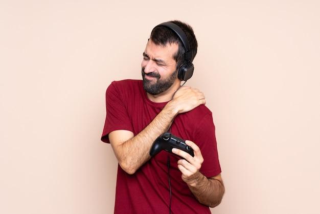 Человек играет с контроллером видеоигры над изолированной стеной, страдающей от боли в плече за усилия