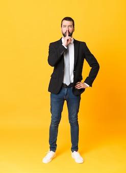 口に指を入れて沈黙ジェスチャーの兆候を示す分離された黄色の上のビジネスの男性の全身ショット