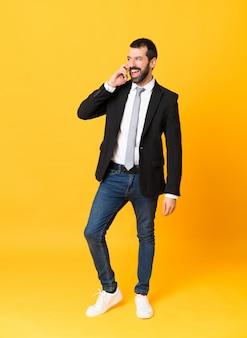 携帯電話との会話を維持する孤立した黄色の上のビジネスの男性の全身ショット