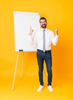 素晴らしいアイデアを指している分離された黄色の上にホワイトボードでプレゼンテーションを行う実業家の全身ショット