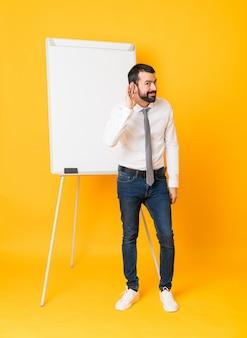 Полнометражный снимок бизнесмена, давая представление на белой доске над изолированных желтый, слушая что-то, положив руку на ухо