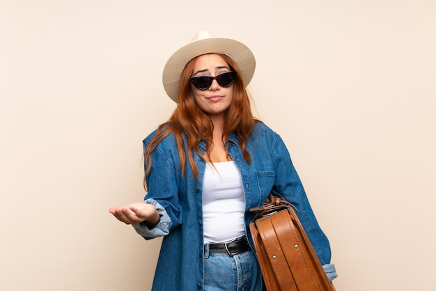 肩を持ち上げながらジェスチャージェスチャーを作るスーツケースで赤毛の旅行者の女の子